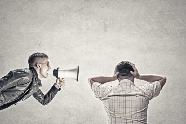 man with loudspeaker talking to another man